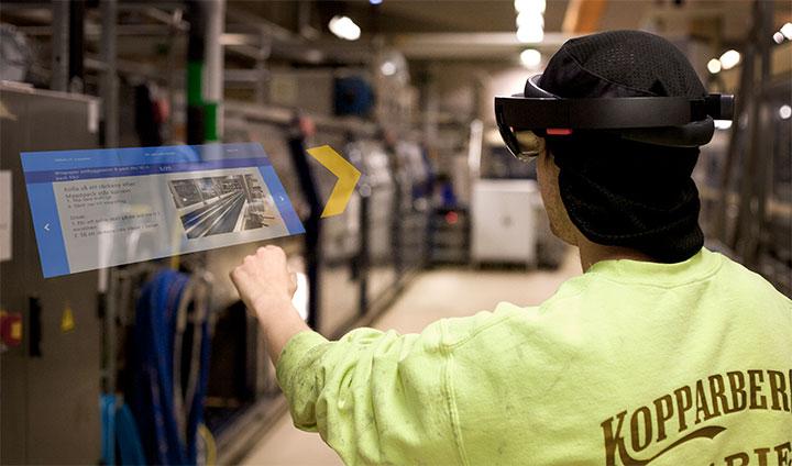 En operatör på Kopparbergs Bryggeri tittar genom AR-glasögon och ser instruktioner dyka upp i luften. Han står i bryggerimiljö.