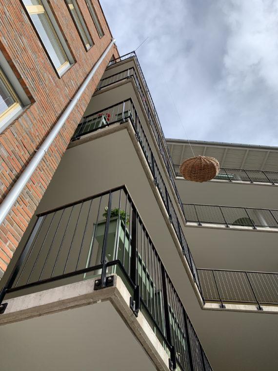 Bilden visar en korg som hissas upp till en balkong med hjälp av ett snöre.