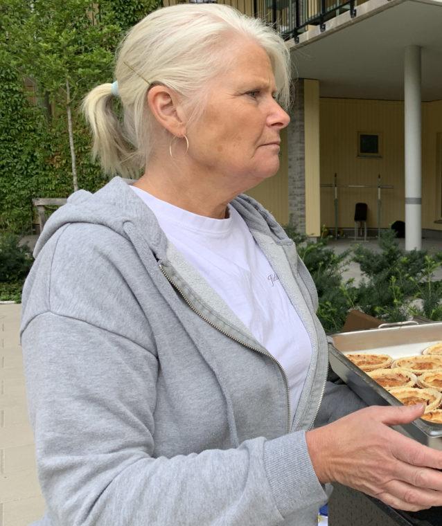 Bilden visar en kvinna som håller i en plåt med minipajer.