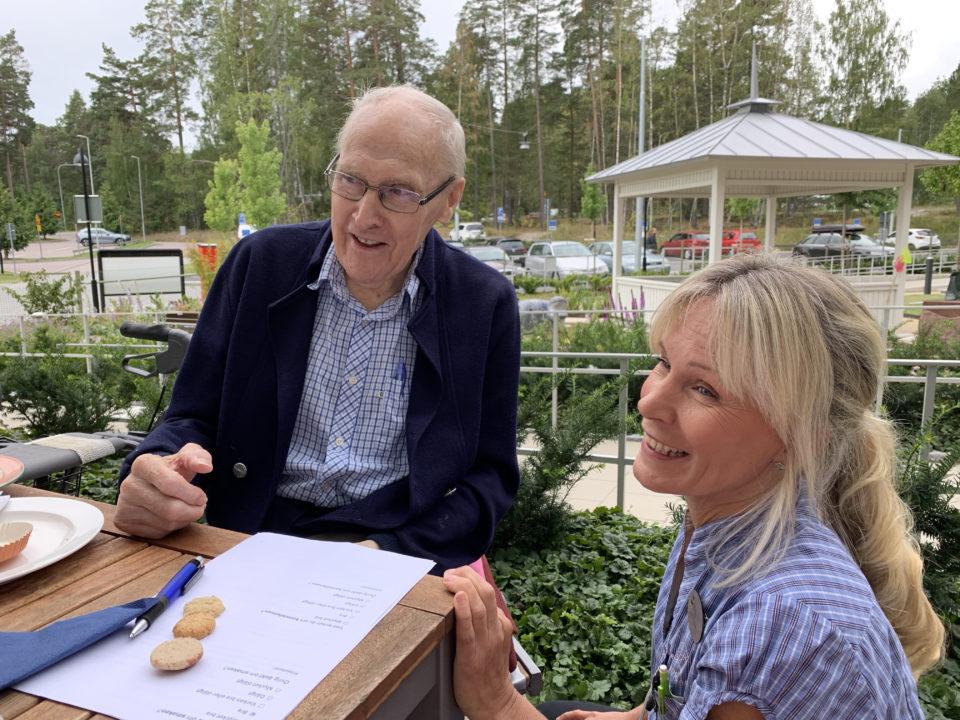 Bilden visar en äldre man och en yngre kvinna som sitter ute vid ett bord.